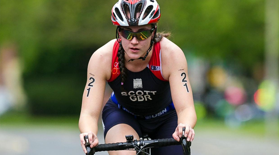 Female athlete cyclist taking part in a triathlon race