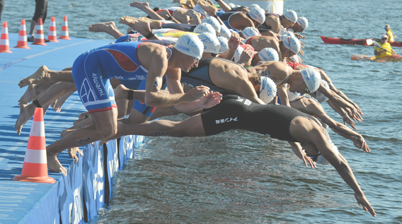 Group of swimmers diving in the sea, ready to start a swimming race