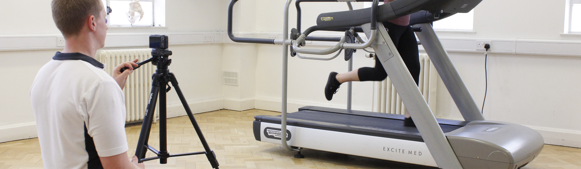 Physiotherapist recording running techniques of athlete on treadmill