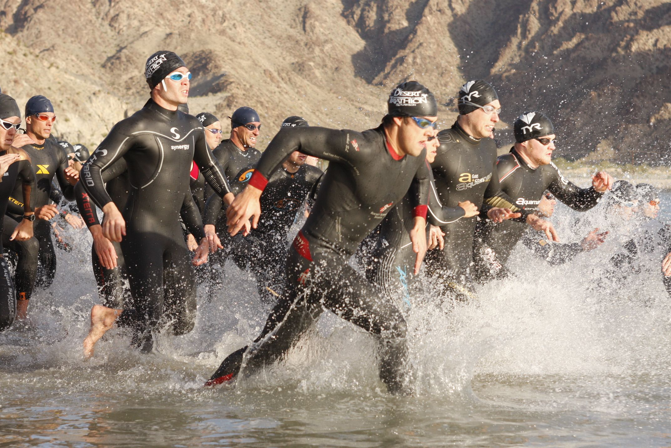 Group of swimmers running towards sea to begin a race