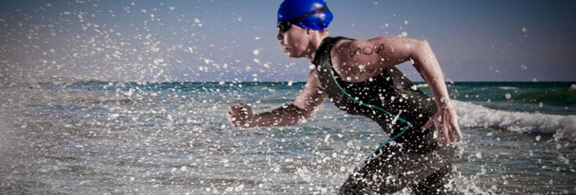 Athlete swimmer running through the water to begin the race