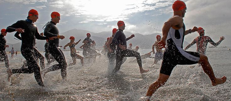 Athletes running through water on beach