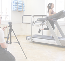 Physiotherapist recording running performance on treadmill