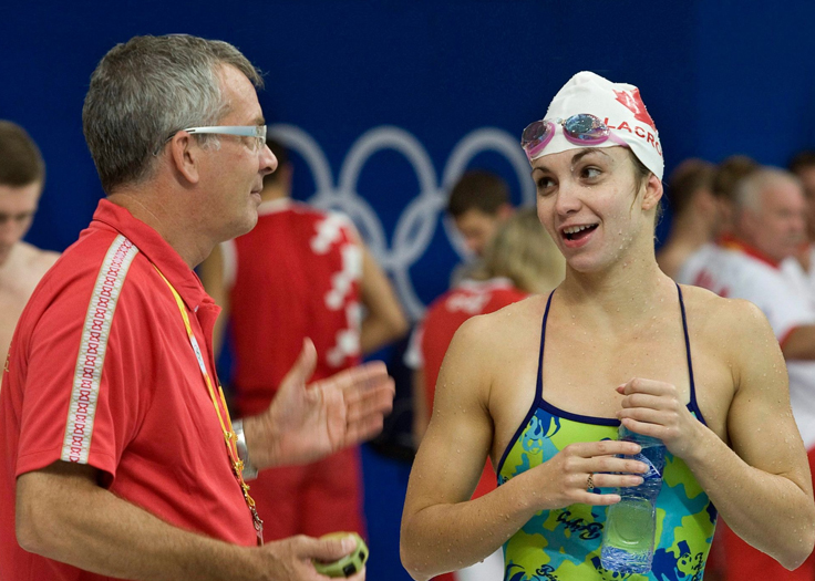 Swimming coach discussing performance with athlete swimmer after race
