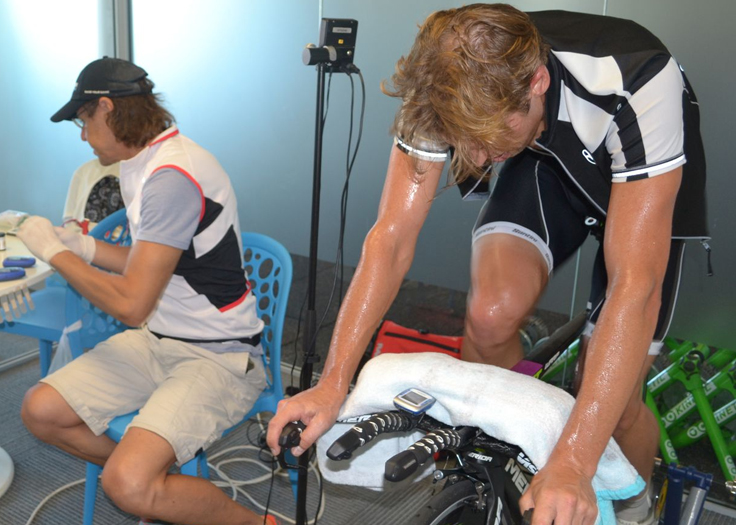 Sport Scientist monitoring performance of athlete on exercise bike