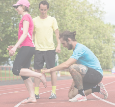 Running Coach providing support for athlete on running track