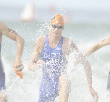 Athlete swimmer running through water to complete triathlon race