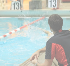 Swimming Coach observing swimmers racing in a pool