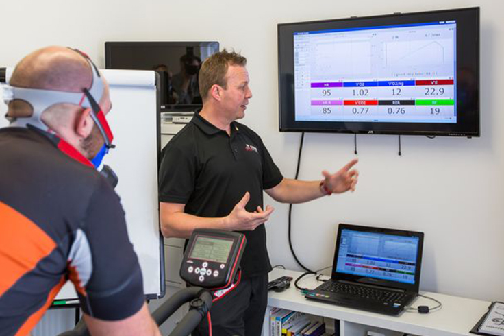 Sports Scientist showing Athlete cyclist results after monitoring performance