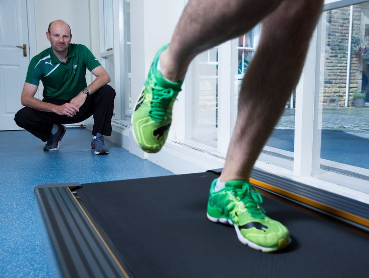 Running coach observing athlete on treadmill