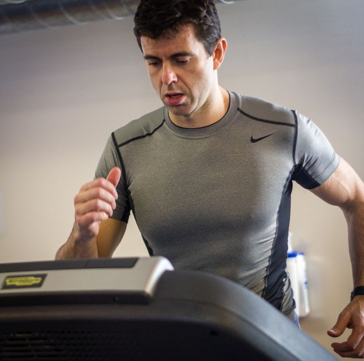 Athlete runner monitoring performance on treadmill