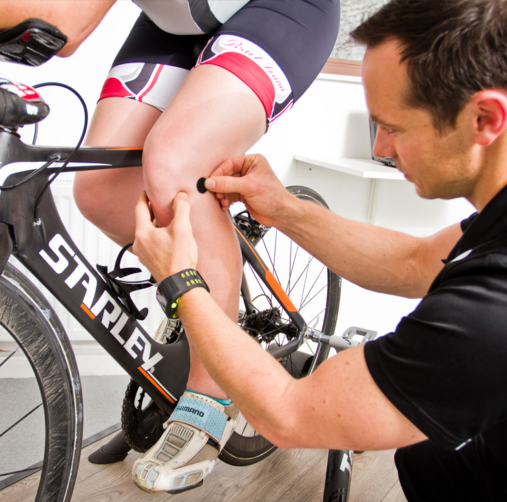 Sports scientist measuring cyclist performance with sensory equipment