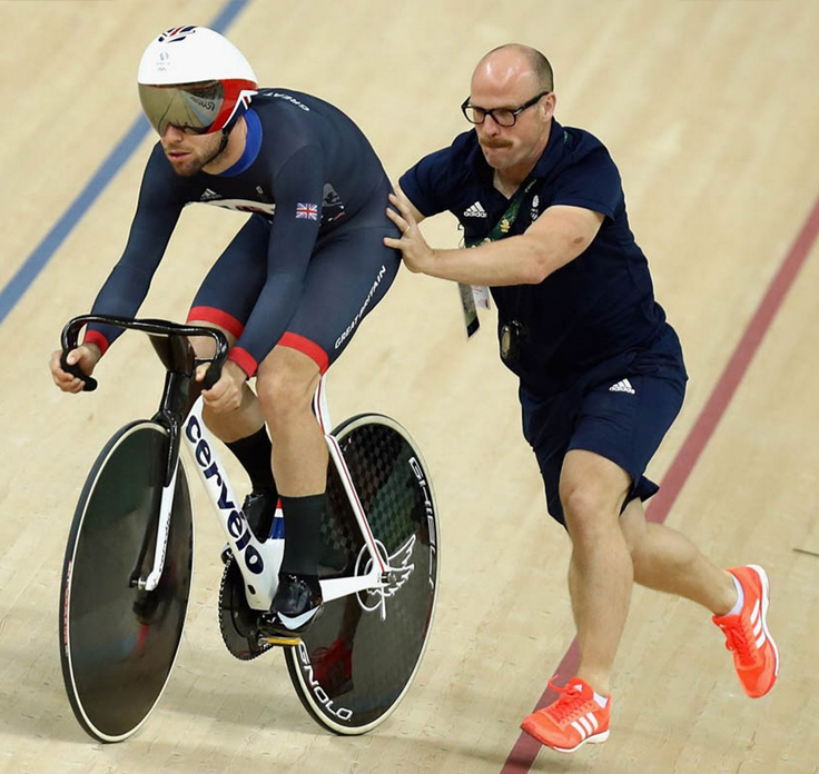 Cycling Coach providing support for athlete cyclist