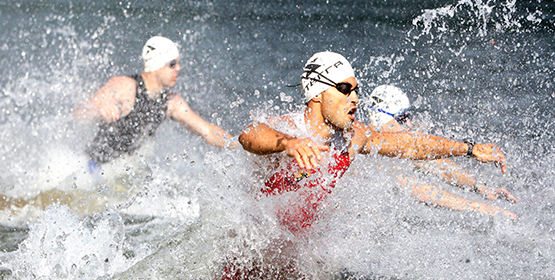 Group of athlete swimmers running into ocean to start race