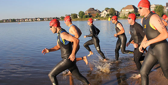 Group of athlete swimmers running into water to start race