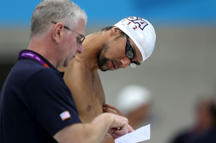 Swimming Coach discussing techniques with athlete swimmer