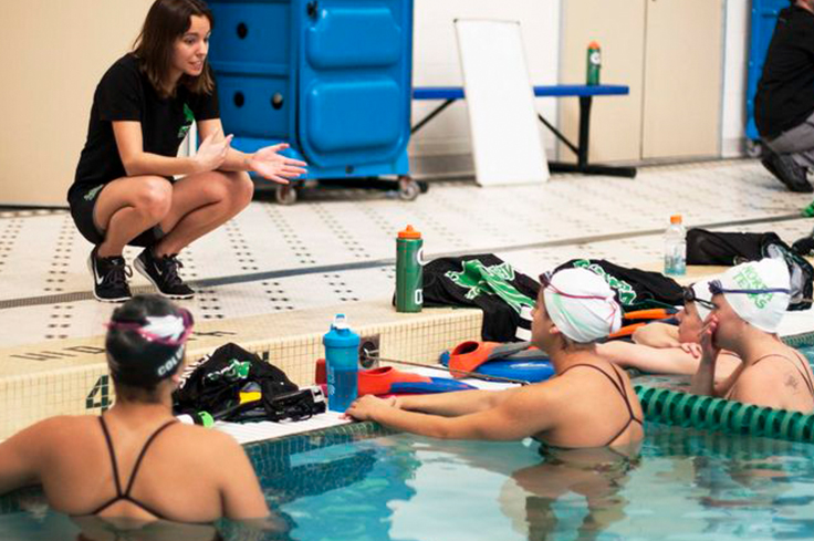 Swimming Coach discussing performance techniques with athlete swimmers in pool