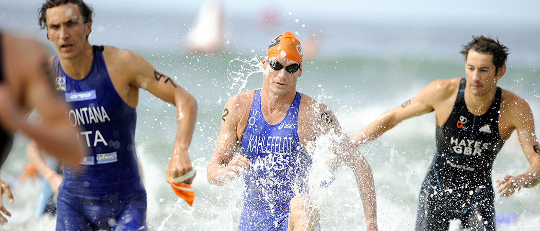 Swimmers running into water for swimming leg of duathlon.