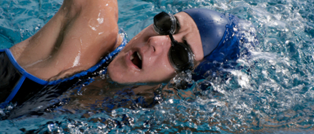 Swimmer taking air between strokes during race.