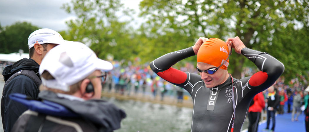 Triathlete preparing for race and putting on swimming goggles.